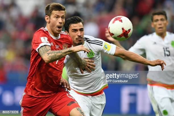 Russia's forward Fedor Smolov vies for the ball against Mexico's defender Diego Reyes during the 2017 Confederations Cup group A football match...