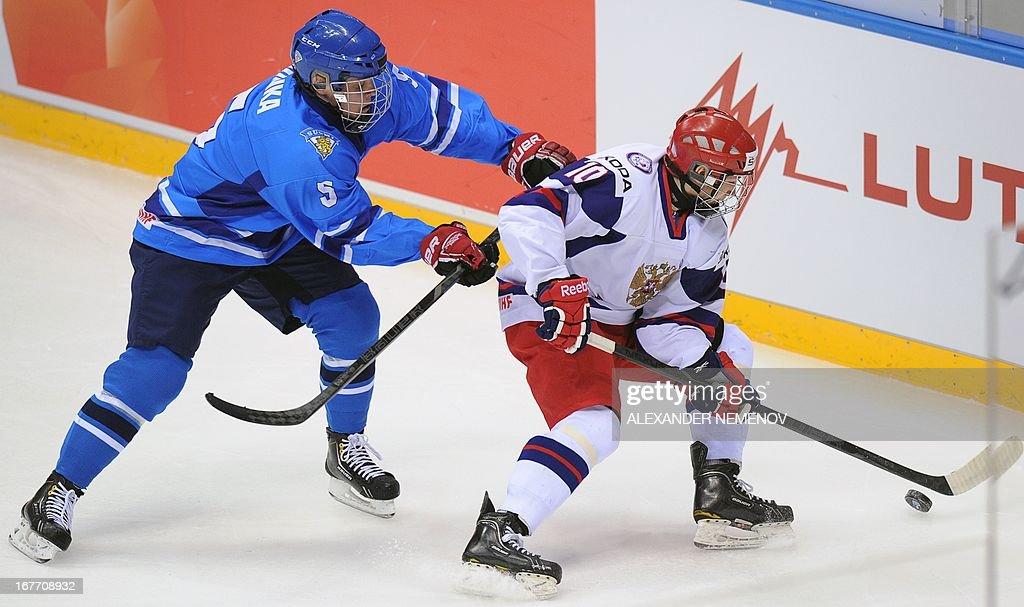 Russia's forward Sergei Tolchinski (R) vies with Finland's defender Julius Honka during their bronze medal game of the IIHF U18 International Ice Hockey World Championship in Sochi on April 28, 2013. AFP PHOTO / ALEXANDER NEMENOV