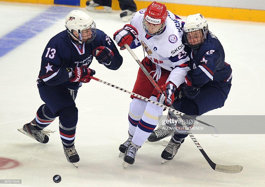 Russia's forward Valeri Nichushkin is sandwiched between US defensman Steven Santini and forward Sean Malone during a semifinal game of the IIHF U18...