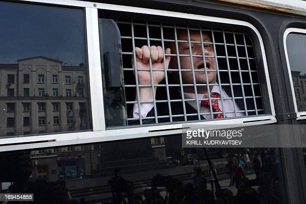 Russia's gay and LGBT rights activist Nikolai Alexeyev speaks from a Russian riot police van during unauthorized gay rights activists rally in cental...