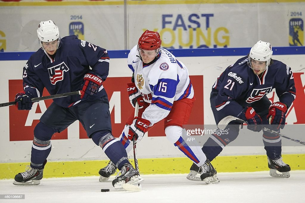 Russia's Georgi Busarov (C) vies with Quentin Shore (L) and Ryan Hartman of the USA during their World Junior Hockey Championships quarter final in Malmo, Sweden on January 2, 2014 OUT