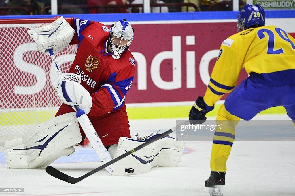 Russia's goalkeeper Andrei Vasilevski (L) saves Sweden's Oskar Sundqvist's shot during the World Junior Hockey Championships semifinal between Sweden and Russia at Malmo Arena in Malmo, Sweden on January 4, 2014.