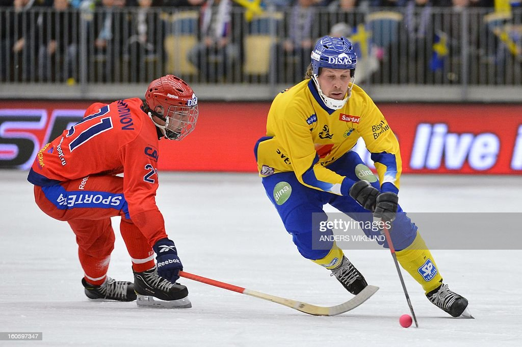 Russia's Igor Larionov and Sweden's Daniel Mossberg (R) vie during Bandy World Championship final match Sweden vs Russia in Vanersborg, Sweden, February 3, 2013.