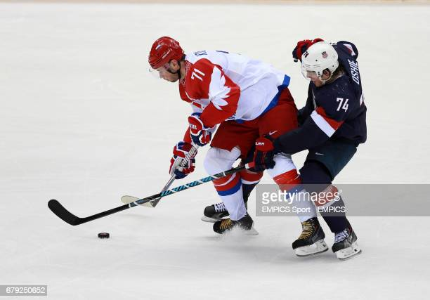 Russia's Ilya Kovalchuk tussles with USA's TJ Oshie in their Preliminary Round match during the 2014 Sochi Olympic Games in Krasnaya Polyana Russia