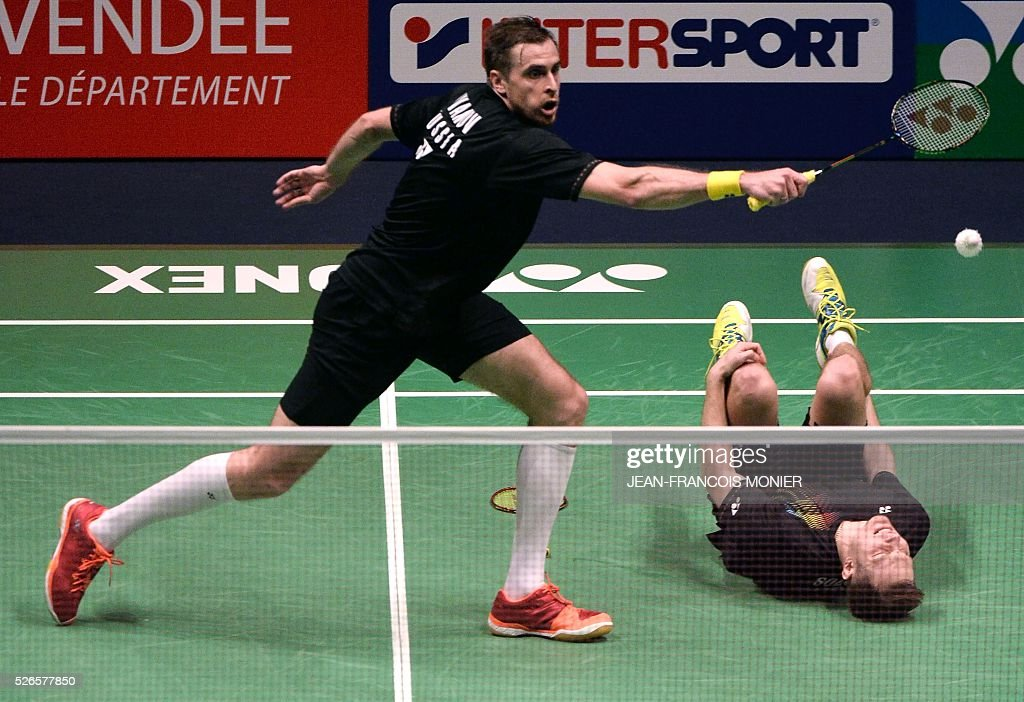 Russia's Ivan Sozonov (R) reacts on the floor as Russia's Vladimir Ivanov (L) hits a return against Denmark's players Kim Astrup and Anders Skaarup Rasmussen during the 2016 European Badminton Championships Men's double semi-final match between Denmark and Russia, on April 30, 2016 in Mouilleron-le-Captif, western France. / AFP / JEAN