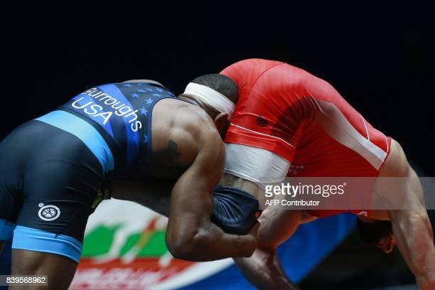 Russia's Khetag Tsabolov challenges USA's Jordan Burroughs during the men's freestyle wrestling 74kg category final at the FILA World Wrestling...