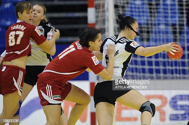 Russia's leftback Liudmila Postnova is pushed by Hungary's Valeria Szabo during the 2012 EHF European Women's Handball Championship Group II match of...