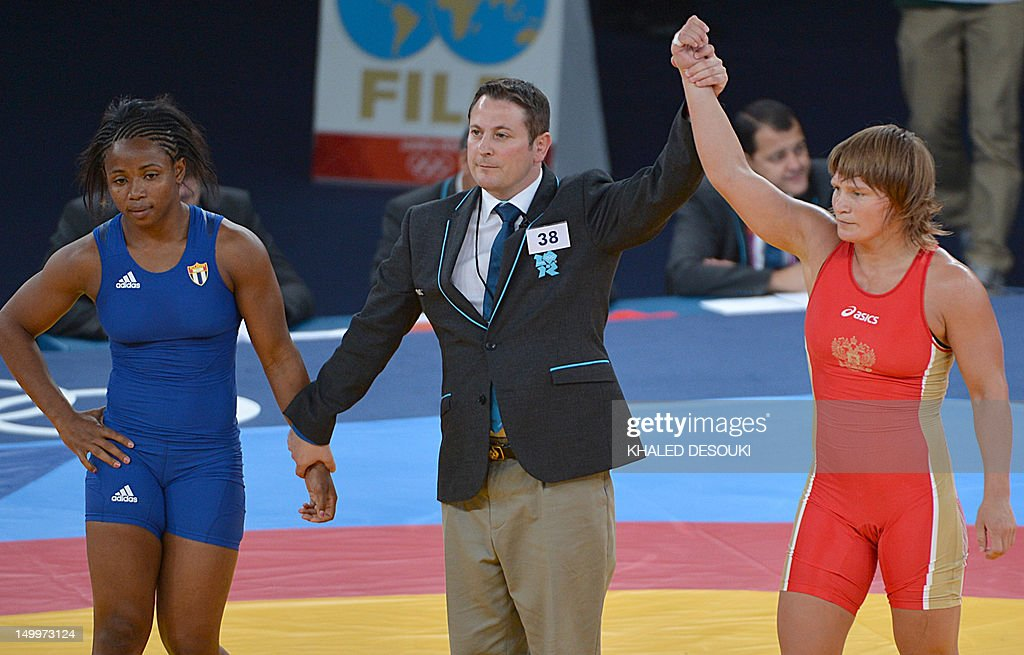 Russia's Lubov Volosova (R) is declared the winner over Cuba's Katerina Vidiaux Lopez (L) in their Women's 63kg Freestyle 1/8 final match on August 8, 2012 during the wrestling event of the London 2012 Olympic Games.