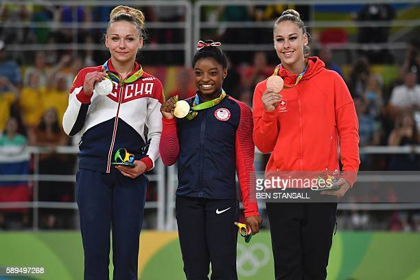 Russia's Maria Paseka US gymnast Simone Biles and Switzerland's Giulia Steingruber celebrate on the podium for the women's vault event final of the...