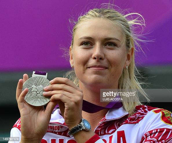 Russia's Maria Sharapova poses on the podium with her silver medal after being defeated by US Serena Williams in the women's singles gold medal match...