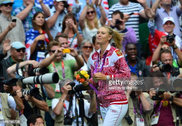 Russia's Maria Sharapova walks with her silver medal after being defeated by US Serena Williams in the women's singles gold medal match of the London...