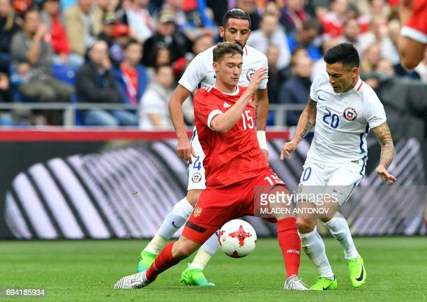 Russia's midfielder Aleksey Miranchuk Chile's defender Mauricio Isla and Chile's midfielder Charles Aranguiz vie for the ball during a friendly...