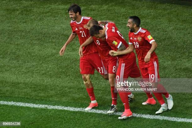 Russia's midfielder Alexander Erokhin Russia's forward Fedor Smolov and Russia's midfielder Alexander Samedov congratulate Russia's midfielder Denis...