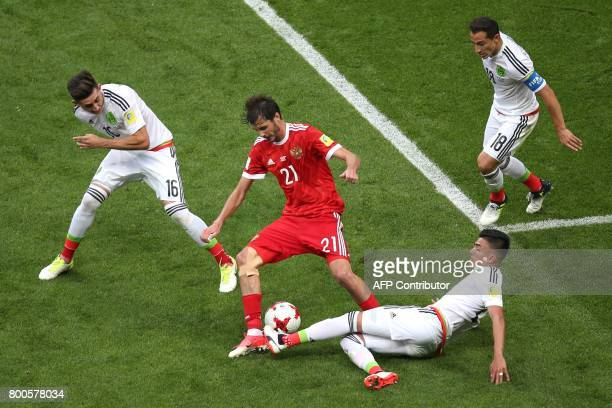 Russia's midfielder Alexander Erokhin vies for the ball against Mexico's midfielder Hector Herrera and Mexico's defender Diego Reyes during the 2017...