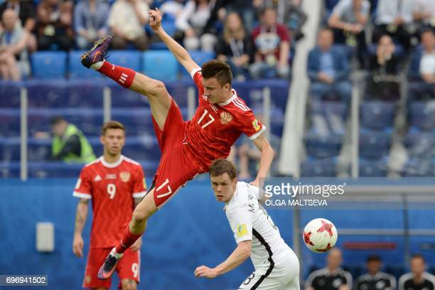Russia's midfielder Alexander Golovin jumps for the ball against New Zealand's midfielder Michael McGlinchey during the 2017 Confederations Cup group...