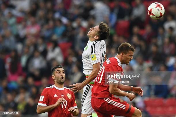 Russia's midfielder Alexander Samedov and forward Maksim Kanunnikov vie for the ball against Mexico's midfielder Hector Herrera during the 2017...