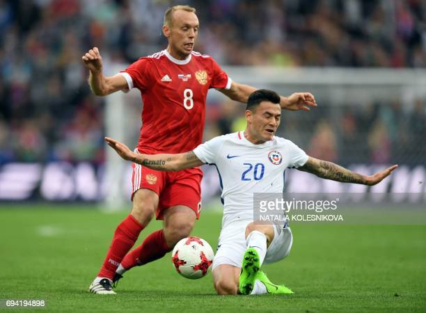 Russia's midfielder Denis Glushakov and Chile's midfielder Charles Aranguiz vie for the ball during a friendly football match between Russia and...