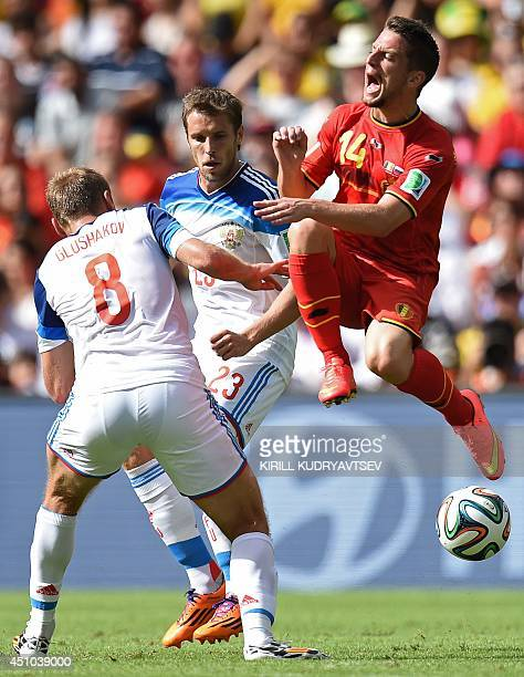 Russia's midfielder Denis Glushakov and Russia's defender Dmitry Kombarov challenge Belgium's forward Dries Mertens for the ball during the Group H...