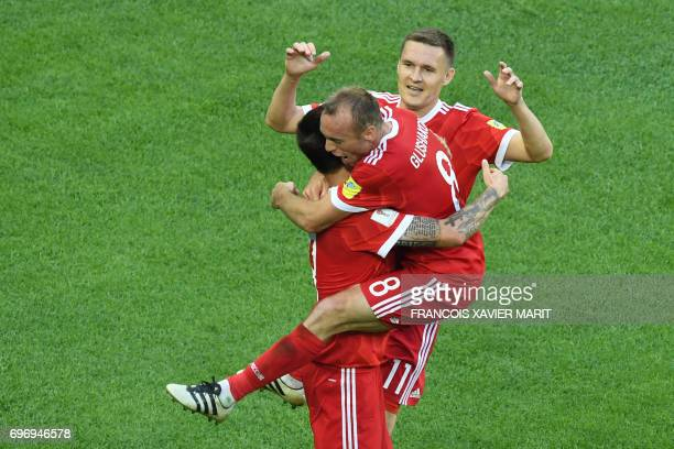 TOPSHOT Russia's midfielder Denis Glushakov hugs Russia's forward Fedor Smolov as they celebrate the team's second goal during the 2017...