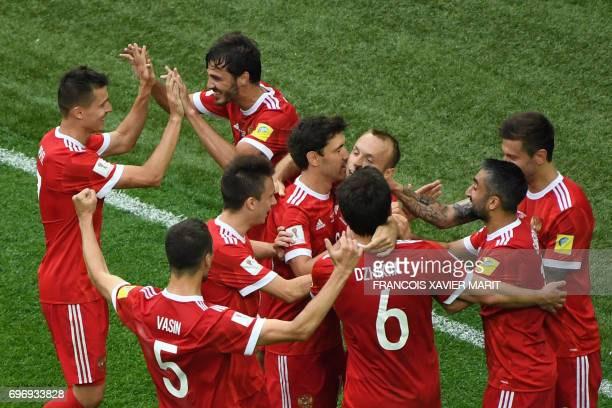 Russia's midfielder Denis Glushakov is congratulated after he scored the first goal of the match during the 2017 Confederations Cup group A football...