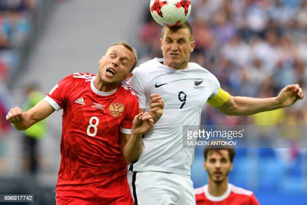 TOPSHOT Russia's midfielder Denis Glushakov jumps for the ball against New Zealand's forward Chris Wood during the 2017 Confederations Cup group A...