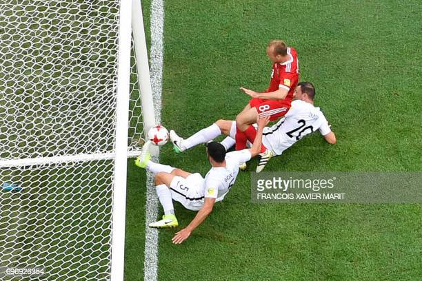 TOPSHOT Russia's midfielder Denis Glushakov scores the match's first goal as he is tackled by New Zealand's defender Michael Boxall and New Zealand's...