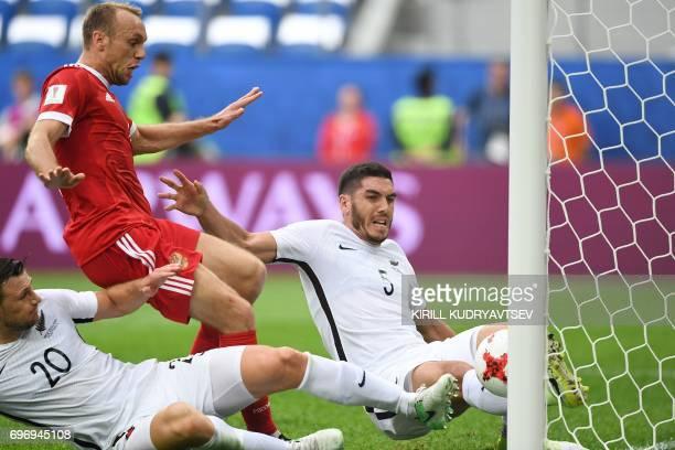 Russia's midfielder Denis Glushakov shoots to score againt New Zealand's defender Tommy Smith and New Zealand's defender Michael Boxall during the...