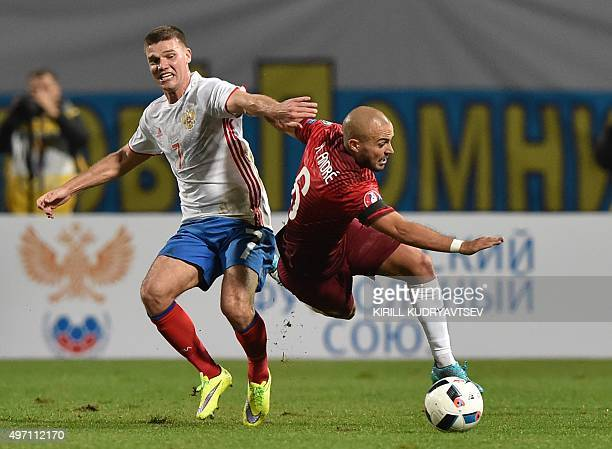 Russia's midfielder Igor Denisov vies for the ball with Portugal's midfielder Andre Andre during the friendly football match between Russia and...