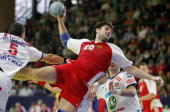 Russia's Mikhail Chipurin scores between Serbia and Montenegro's Marko Krivokapi and compatriot Alem Toskic during their game at the main round of...