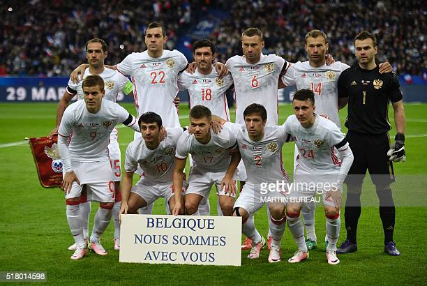 Russia's national football team poses for a team picture with a sign reading 'Belgium we are with you' ahead of the international friendly football...