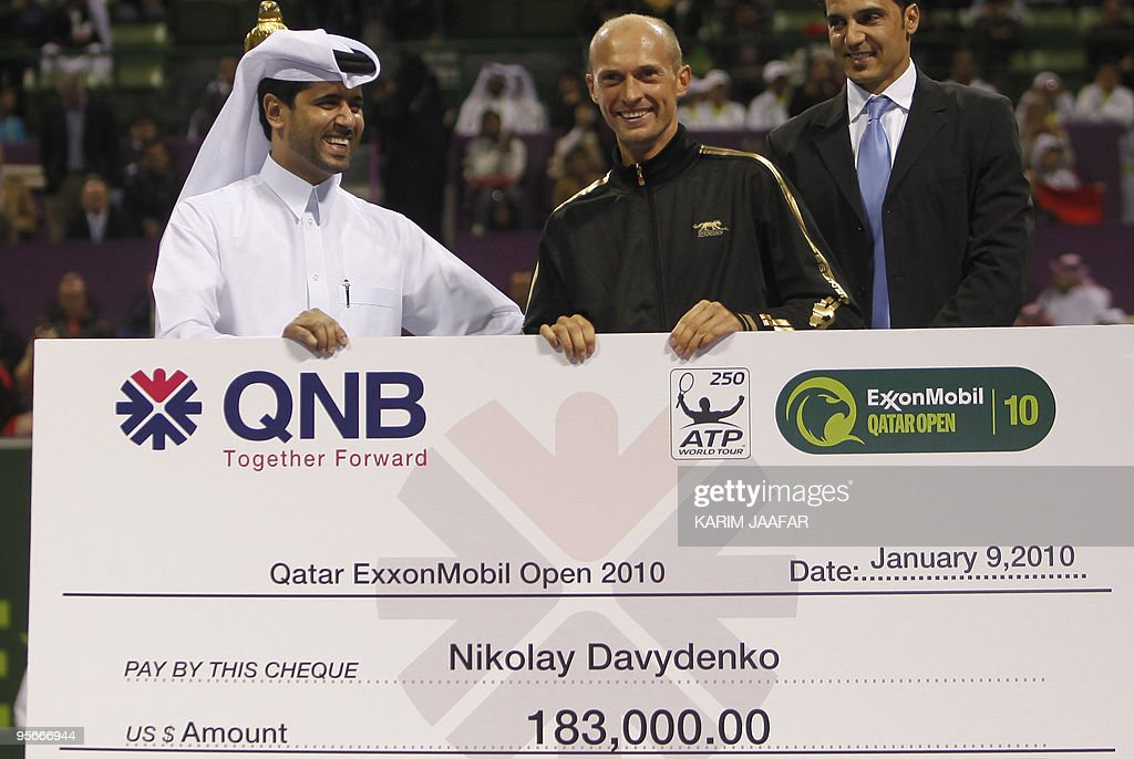 Russia's Nikolay Davydenko receives the winner's cheque from Sheikh Nasser alKhulaifi the president of Qatar's Tennis Federation after beating...