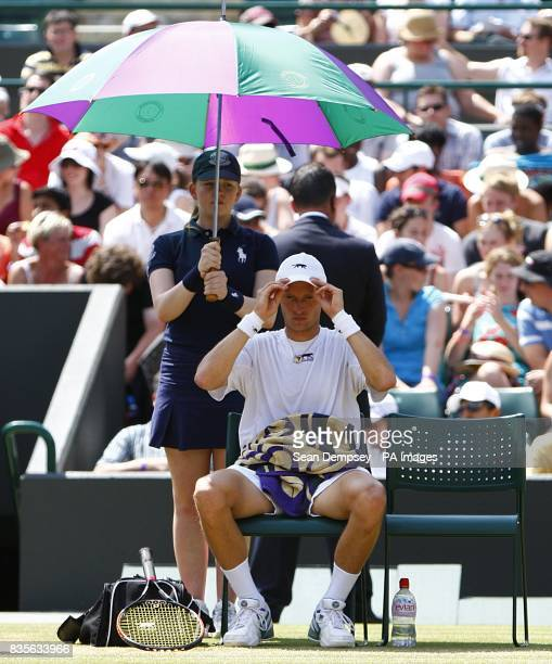 Russia's Nikolay Davydenko shelters under an umbrella during a break in his mach against Czech Republic's Tomas Berdych during the Wimbledon...