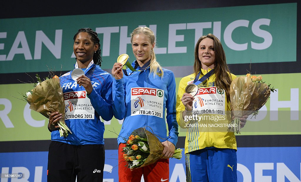 Russia's Olga Kucherenko (C) celebrates winning the women's Long Jump final on the podium with second placed France's Eloyse Lesueur (L) and third placed Sweden's Erica Jarder (R) at the European Indoor athletics Championships in Gothenburg, Sweden, on March 2, 2013.