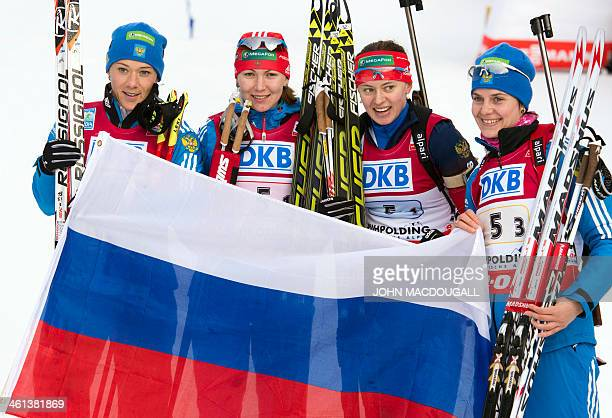 Russia's Olga Zaitseva Ekaterina Glazyrina Olga Vilukhina and Irina Starykh pose with a flag after taking the first place in the Women's 4x6 Km relay...