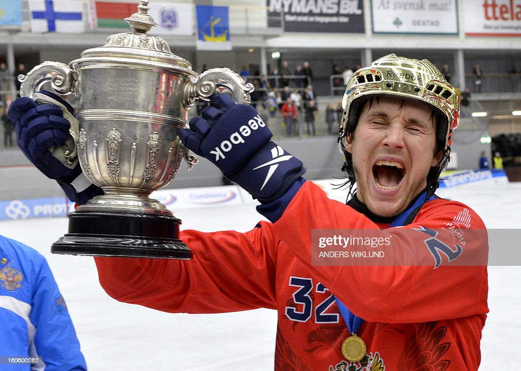 Russia's Pavel Bulatov raises the trophy as he celebrates their 4-3 victory in the Bandy World Championship final match Sweden vs Russia in Vanersborg, Sweden, February 3, 2013.
