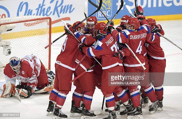 Russia's players celebrate their team's winning goal behind Denmark's goalie Thomas Lillie during the 2016 IIHF World Junior Ice Hockey Championship...