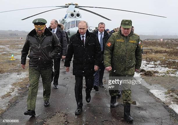 Russia's President Vladimir Putin and Defence Minister Sergei Shoigu walk to watch military exercises upon his arrival at the Kirillovsky firing...