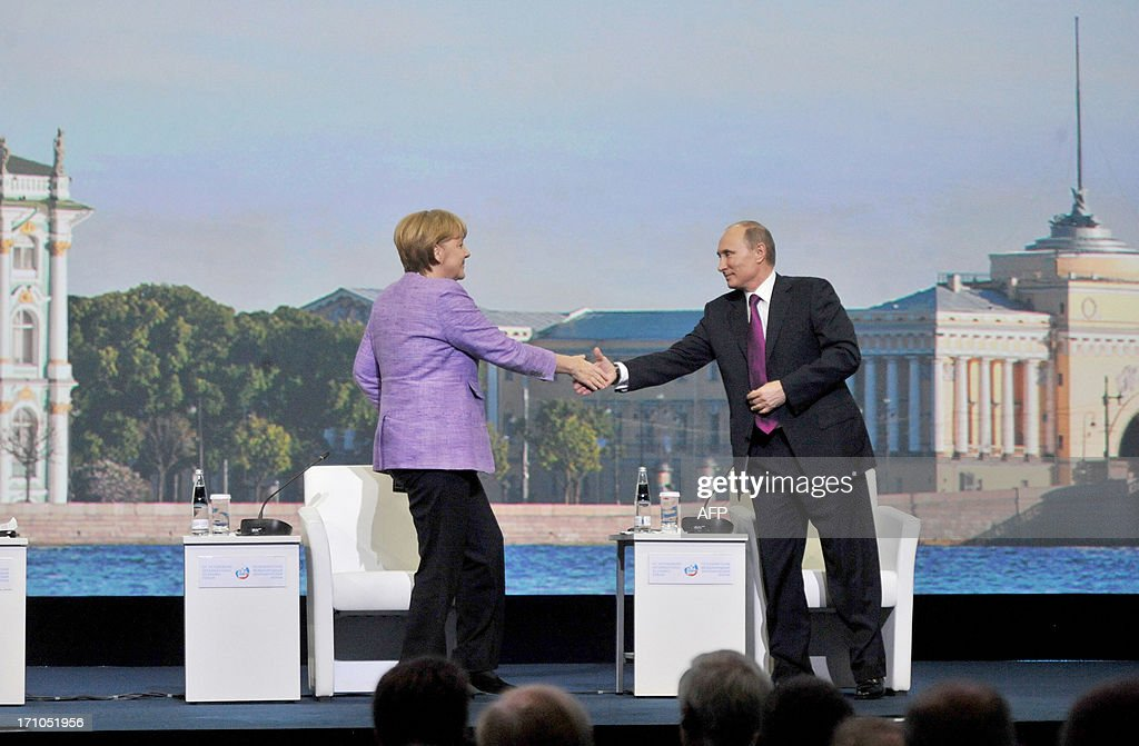 Russia's President Vladimir Putin (R) and Germany's Chancellor Angela Merkel shake hands as they attend an International Economic Forum in St. Petersburg, on June 21, 2013. Putin and Merkel announced today that they would both attend the opening of a Saint Petersburg exhibition including treasures taken by the Red Army at the end of World War II. German officials had said earlier their visit to the 'Bronze Age of Europe -- Europe Without Borders' exhibition at the Hermitage museum had been scrapped due to what German media said was a wrangle over the future of the so-called trophy art.