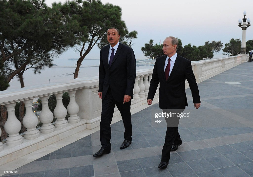 Russia's President Vladimir Putin (R) and his Azerbaijani counterpart Ilham Aliyev (L) walk in Baku, on August 13, 2013. Russian crude giant Rosneft signed yesterday an oil and gas agreement with Azerbaijan's state energy firm aimed at loosening the European Union's ties with the key Caspian market. Neither side disclosed the full details of a deal that was sealed on the sidelines of talks in Baku between visiting Putin and Aliyev. AFP PHOTO/ RIA-NOVOSTI/ POOL/ MIKHAIL KLIMENTYEV