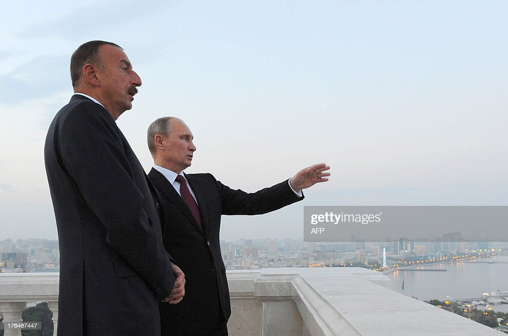 Russia's President Vladimir Putin (L) and his Azerbaijani counterpart Ilham Aliyev (R) speak as they walk in Baku, on August 13, 2013. Russian crude giant Rosneft signed yesterday an oil and gas agreement with Azerbaijan's state energy firm aimed at loosening the European Union's ties with the key Caspian market. Neither side disclosed the full details of a deal that was sealed on the sidelines of talks in Baku between visiting Putin and Aliyev.