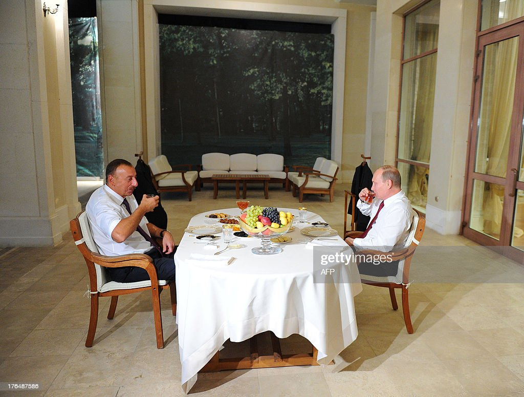 Russia's President Vladimir Putin (R) and his Azerbaijani counterpart Ilham Aliyev speak during a tea party at the Zagulba State residence in Baku, on August 13, 2013. Russian crude giant Rosneft signed yesterday an oil and gas agreement with Azerbaijan's state energy firm aimed at loosening the European Union's ties with the key Caspian market. Neither side disclosed the full details of a deal that was sealed on the sidelines of talks in Baku between visiting Putin and Aliyev.