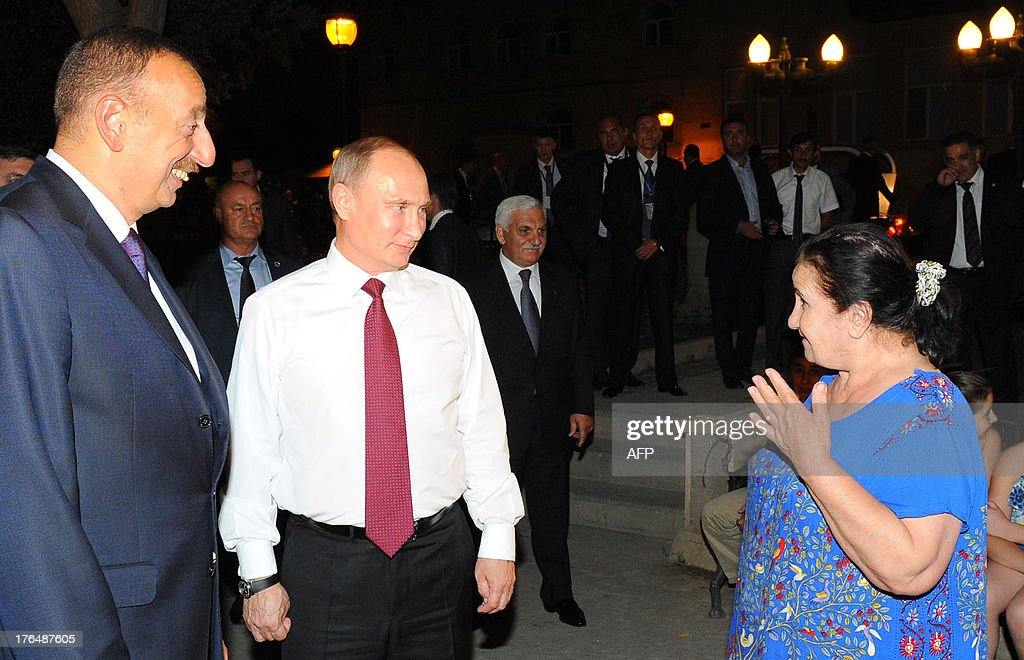 Russia's President Vladimir Putin (2nd L) and his Azerbaijani counterpart Ilham Aliyev (L) speak with a local resident during their walk in Baku, on August 13, 2013. Russian crude giant Rosneft signed yesterday an oil and gas agreement with Azerbaijan's state energy firm aimed at loosening the European Union's ties with the key Caspian market. Neither side disclosed the full details of a deal that was sealed on the sidelines of talks in Baku between visiting Putin and Aliyev.