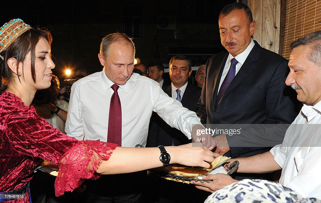 Russia's President Vladimir Putin (2nd L) and his Azerbaijani counterpart Ilham Aliyev (2nd R) speak with local residents during their walk in Baku, on August 13, 2013. Russian crude giant Rosneft signed yesterday an oil and gas agreement with Azerbaijan's state energy firm aimed at loosening the European Union's ties with the key Caspian market. Neither side disclosed the full details of a deal that was sealed on the sidelines of talks in Baku between visiting Putin and Aliyev. AFP PHOTO/ RIA-NOVOSTI/ POOL/ MIKHAIL KLIMENTYEV