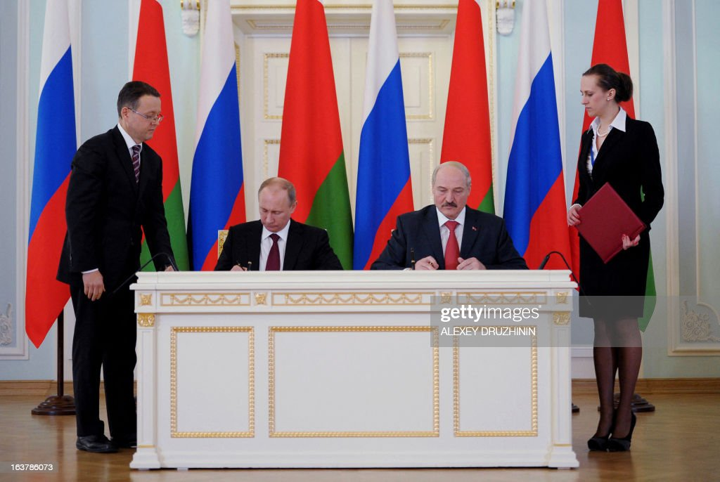 Russia's President Vladimir Putin (2nd L) and his Belarus counterpart Alexander Lukashenko (2nd R) sign documents at the Konstantinovsky palace in Strelna just outside St.Petersburg, on March 15, 2013, after a meeting of the Russia-Belarus Union State's Supreme State Council .