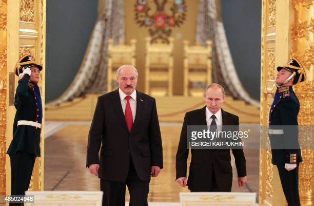 Russia's President Vladimir Putin and his Belarus' counterpart Alexander Lukashenko walk past honor guards as they attend a session of the Supreme...