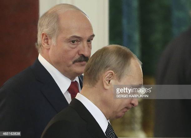 Russia's President Vladimir Putin and his Belarus' counterpart Alexander Lukashenko walk as they attend a session of the Supreme State Council of the...