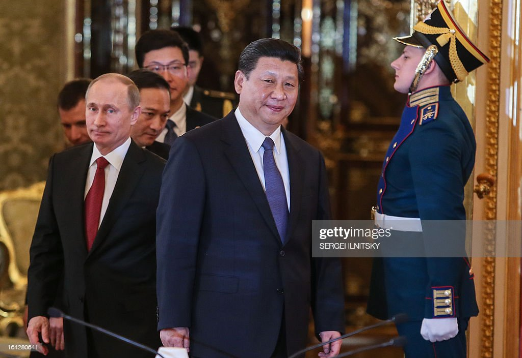 Russia's President Vladimir Putin (R) and his Chinese counterpart Xi Jinping (C) enter a hall as they meet in the Grand Kremlin Palace in Moscow, on March 22, 2013. Xi Jinping arrived today in Moscow on his first foreign trip, to cement ties between the two countries by inking a raft of energy and investment accords. AFP PHOTO / POOL/ SERGEI ILNITSKY