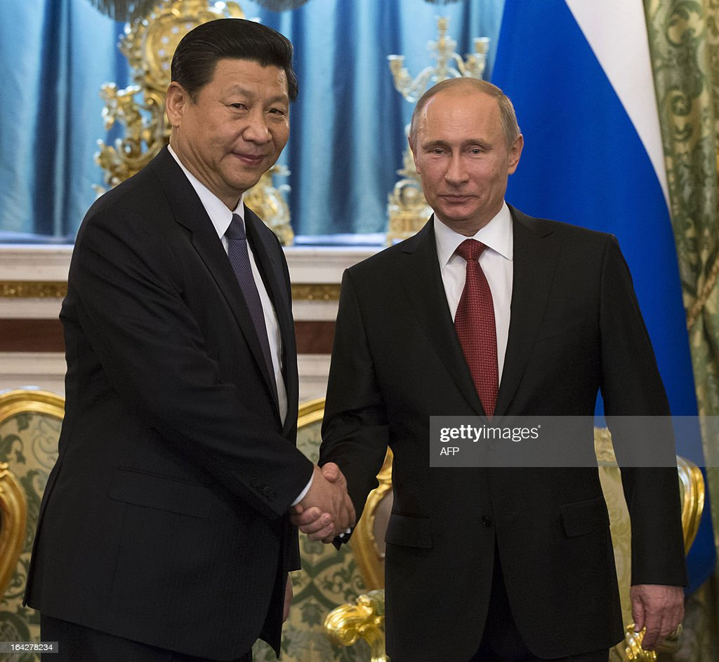 Russia's President Vladimir Putin (R) and his Chinese counterpart Xi Jinping shake hands during their meeting in the Grand Kremlin Palace in Moscow, on March 22, 2013. Xi Jinping arrived today in Moscow on his first foreign trip, to cement ties between the two countries by inking a raft of energy and investment accords.