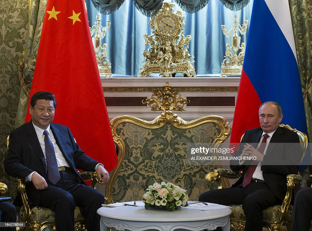 Russia's President Vladimir Putin (R) and his Chinese counterpart Xi Jinping speak during their meeting in the Grand Kremlin Palace in Moscow, on March 22, 2013. Xi Jinping arrived today in Moscow on his first foreign trip, to cement ties between the two countries by inking a raft of energy and investment accords.