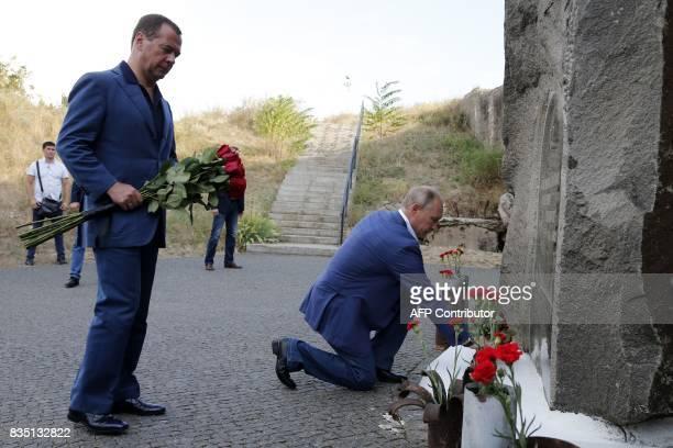 Russia's President Vladimir Putin and Russia's Prime Minister Dmitry Medvedev lay flowers to a monument to defenders of Sevastopol at the 35th...
